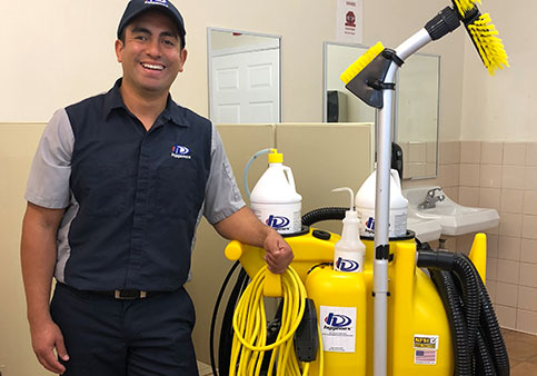 Hygenex employee standing next to cleaning equipment